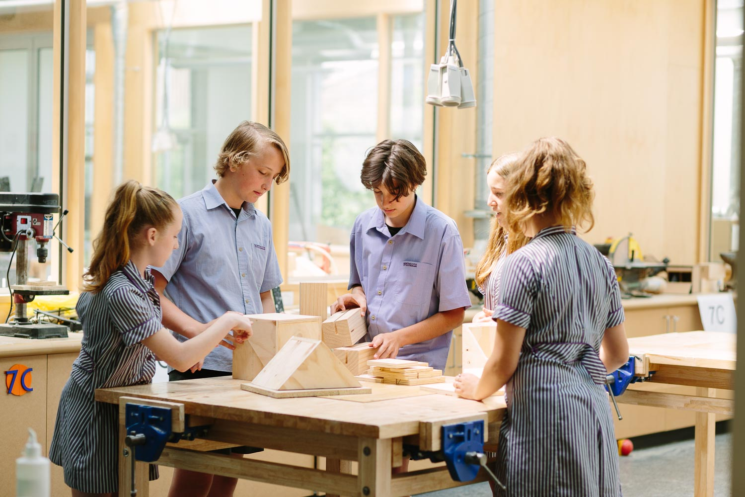 Group of students working on a wooden design