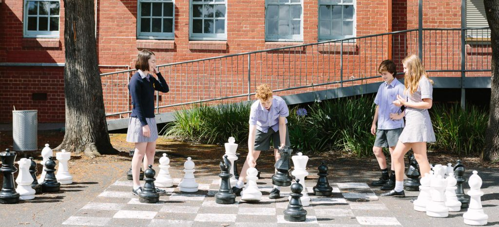 Students playing giant chess